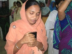 One of Pastor John's converts clutches her Talking Bible during the service.