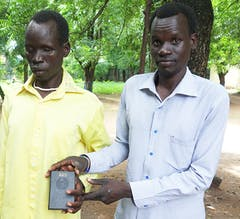 Bup, with a sighted man, holds a Talking Bible and smiles