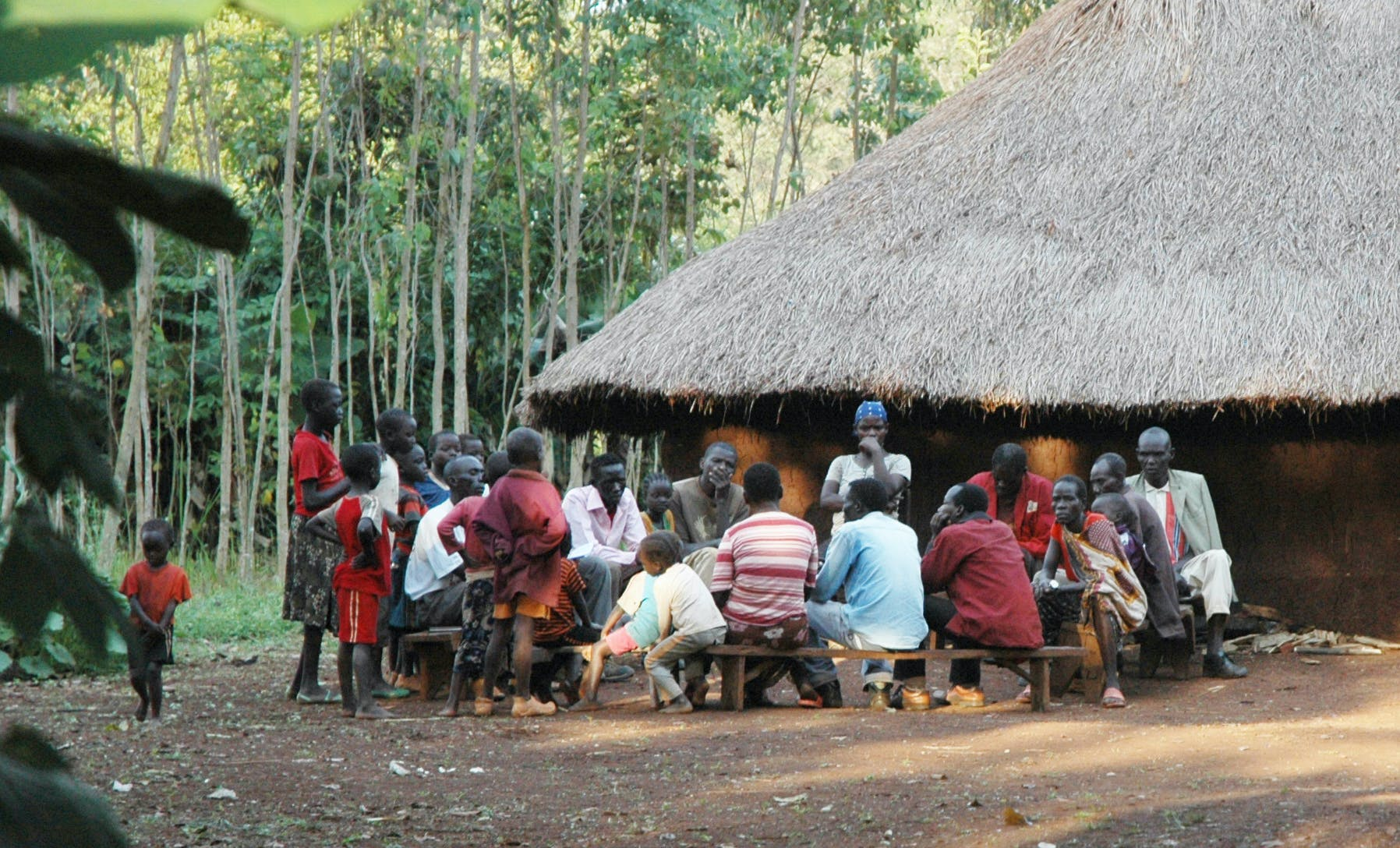 Borana people sitting outside a hut