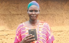 Mary holding her Talking Bible in front of a mud hut.