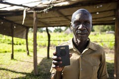 Samson holding a Talking Bible under a hut.