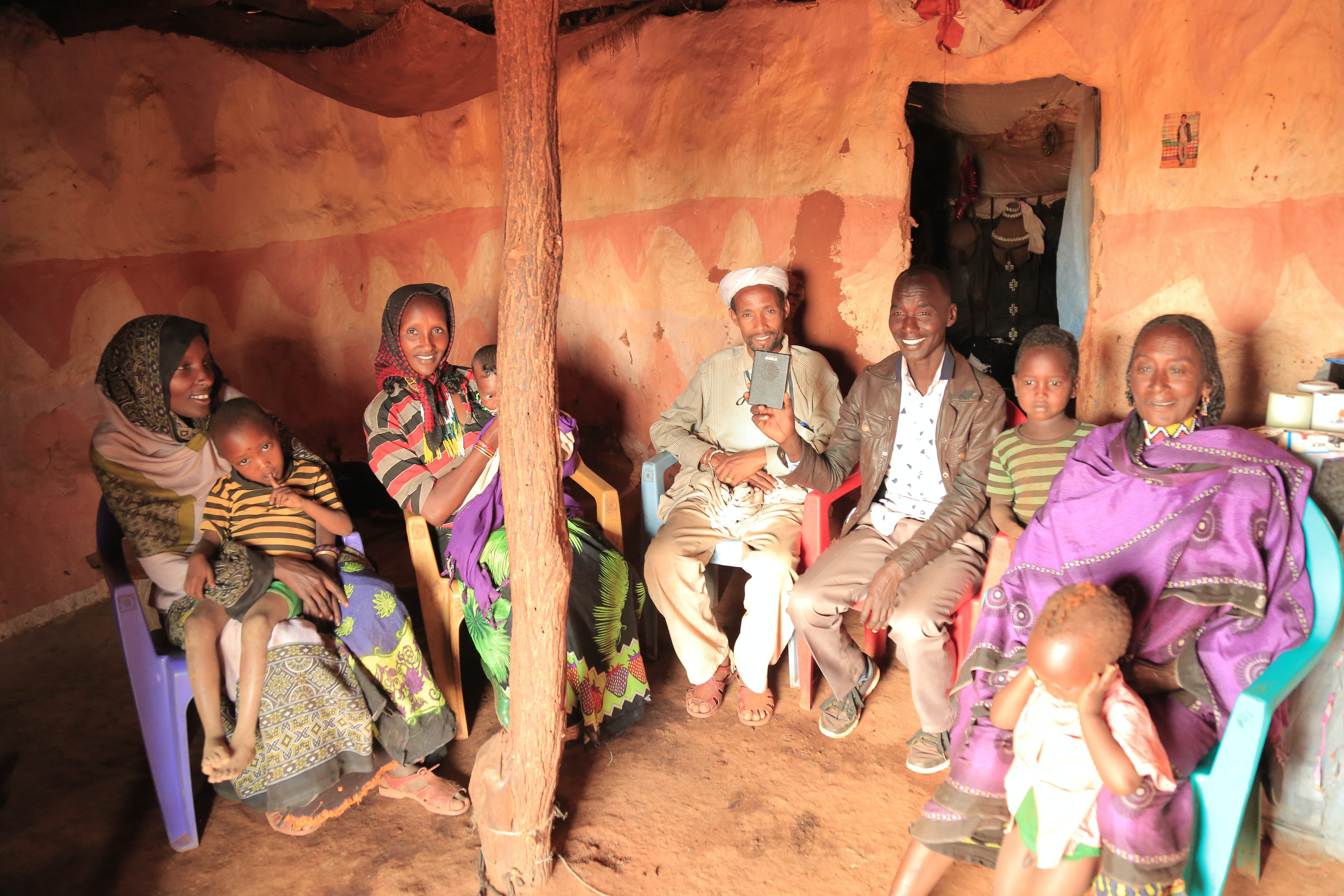 Group inside a hut listening to a Talking Bible