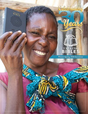 African woman wearing pink and blue holding a Talking Bible - Cover of Winter-Spring 2020 Newsletter