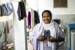 Martha smiles and holds up Talking Bible near some laundry hanging to dry